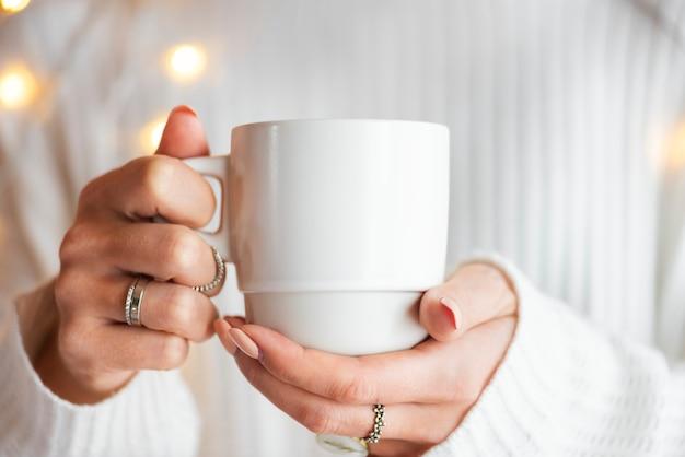 Mulher com um suéter branco e uma maquete de xícara branca