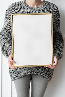 Mulher com um suéter preto segurando uma maquete de moldura de madeira