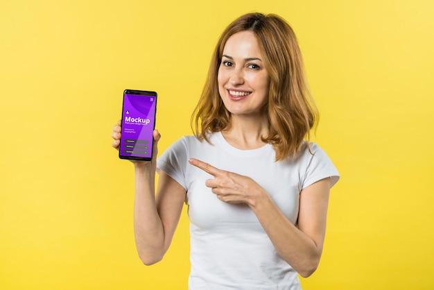 Mulher com vista frontal segurando um telefone celular