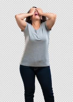 Mulher de meia idade frustrada e desesperada, irritada e triste com as mãos na cabeça