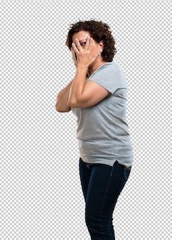 Mulher de meia idade se sente preocupada e assustada, olhando e cobrindo o rosto, medo e ansiedade