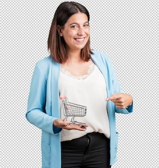 Mulher de meia idade sorrindo e feliz, segurando um carrinho de compras em miniatura, conceito de compras, consumismo