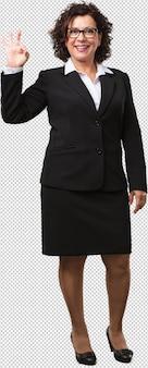 Mulher de negócios de meia-idade de corpo inteiro alegre e confiante fazendo okey gesto, animado e gritando, conceito de aprovação e sucesso
