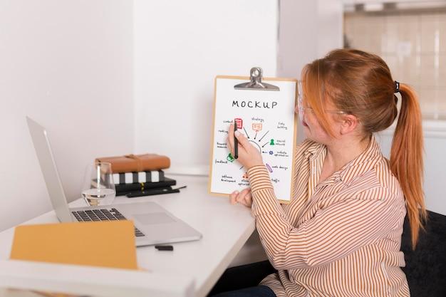 Mulher de negócios mostrando sua maquete de prancheta em uma videoconferência