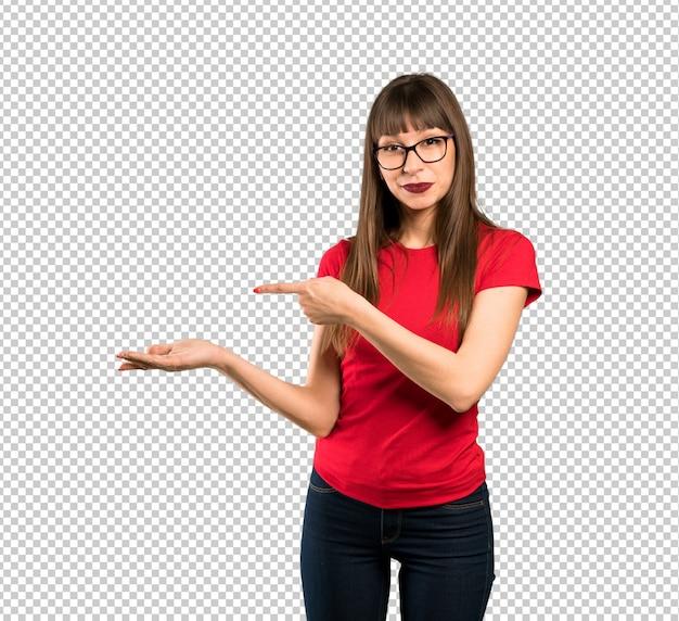 Mulher de óculos segurando copyspace imaginário na palma da mão para inserir um anúncio