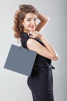 Mulher de preto com sacola de compras.