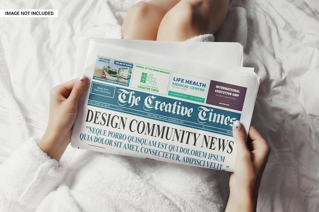 Mulher de roupão lendo uma maquete de jornal