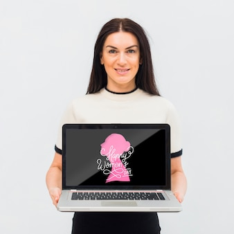 Mulher de tiro médio com laptop dentro de casa