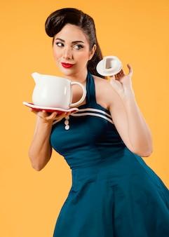 Mulher de tiro médio segurando a maquete do bule de chá