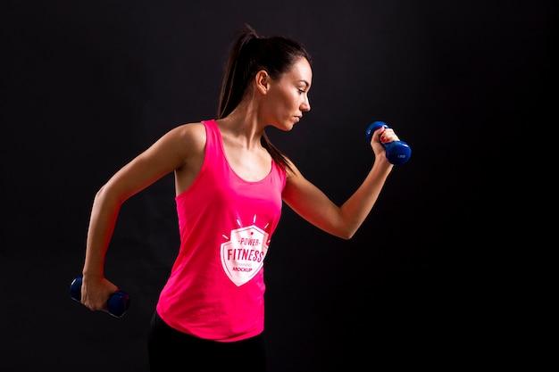 Mulher de tiro médio segurando halteres