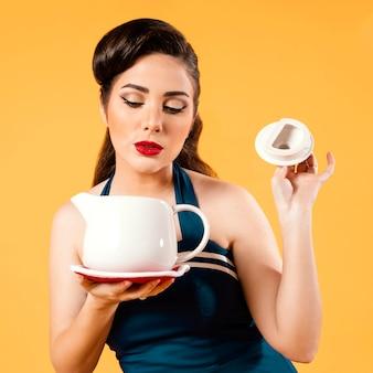 Mulher de tiro médio segurando o bule de chá