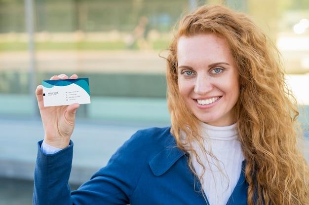 Mulher de tiro médio segurando um cartão de visita