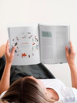 Mulher deitada e lendo uma revista mock up