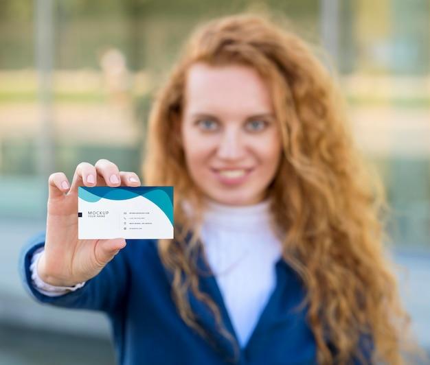 Mulher desfocada com tiro médio segurando um cartão de visita