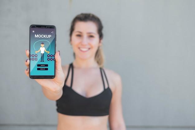 Mulher desfocada em roupas esportivas segurando uma maquete de celular