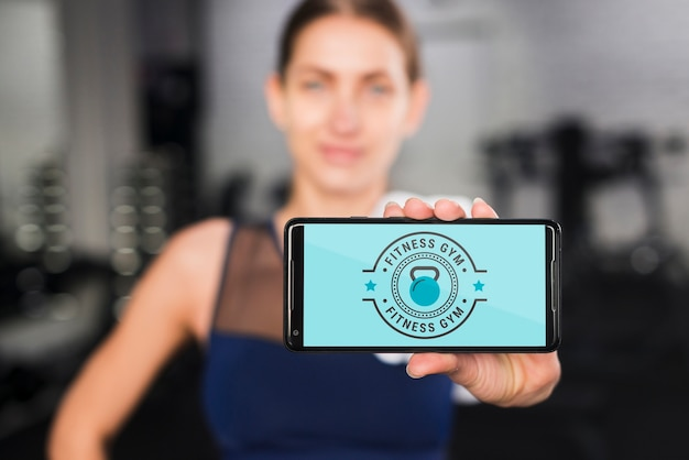 Mulher desportiva feliz apresentando maquete de smartphone