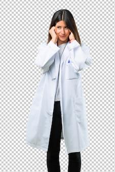 Mulher do doutor com o estetoscópio que cobre ambas as orelhas com as mãos. expressão frustrada