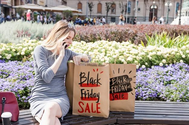 Mulher, em, cidade, com, pretas, sexta feira, sacolas