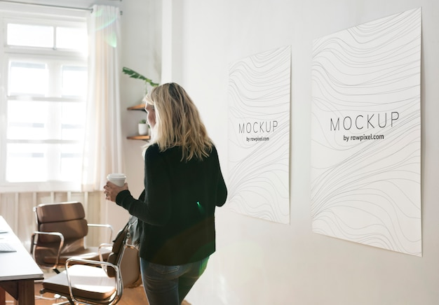 Mulher em um espaço de trabalho com maquetes de design de cartaz