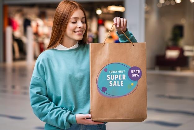 Mulher em um shopping, segurando um grande saco de papel cheio de produtos à venda