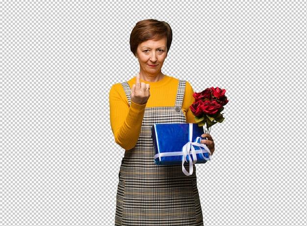 Mulher envelhecida média que comemora o dia dos namorados que convida a vir