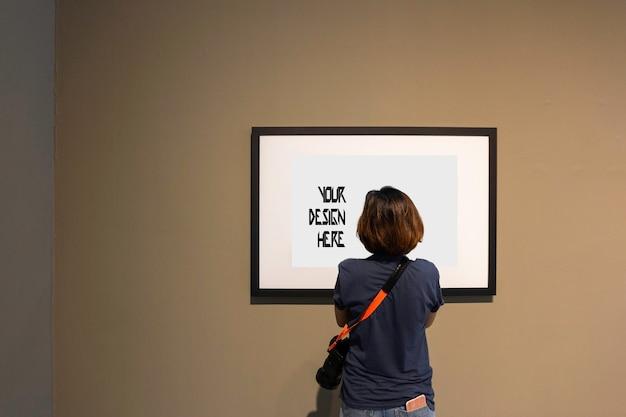Mulher está olhando para moldura em branco na parede na galeria de arte