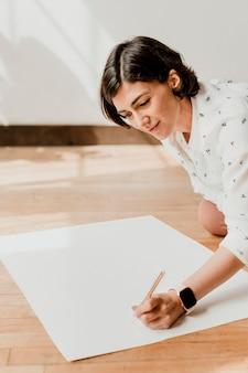 Mulher feliz escrevendo em uma maquete de papel gráfico branco
