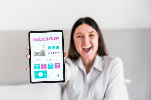 Mulher feliz segurando tablet com maquete