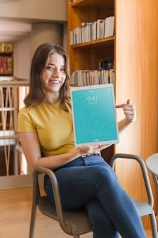 Mulher feliz, segurando, tabuleta, maquete, em, biblioteca