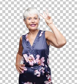 Mulher fresca superior que sorri e que olha satisfeita e feliz, contando o número três com dedos.