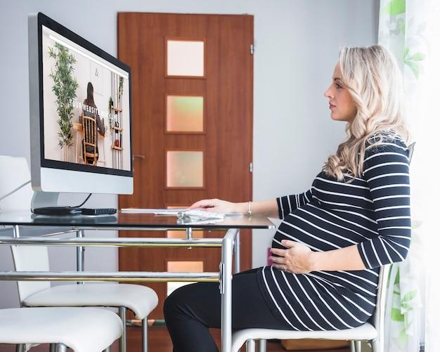 Mulher grávida, usando computador