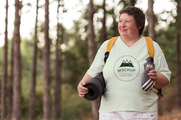 Mulher idosa acampando com um mock-up de camiseta