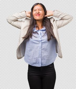 Mulher indiana de negócios jovem cobrindo os ouvidos com as mãos, zangado e cansado de ouvir algum som