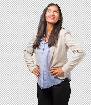Mulher indiana de negócios jovem com as mãos nos quadris, em pé, relaxado e sorridente