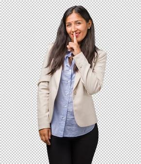 Mulher indiana de negócios jovem mantendo um segredo ou pedindo silêncio, rosto sério, conceito de obediência