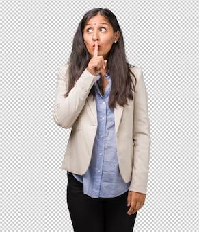 Mulher indiana de negócios jovem manter um segredo ou pedindo silêncio, cara séria, conceito de obediência