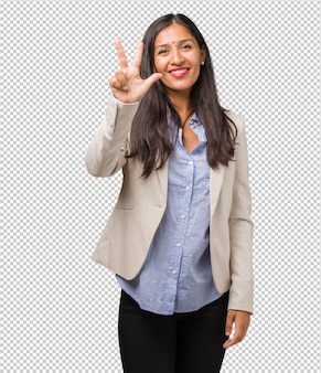Mulher indiana de negócios jovem mostrando o número três, símbolo de contagem, conceito de matemática, confiante e alegre