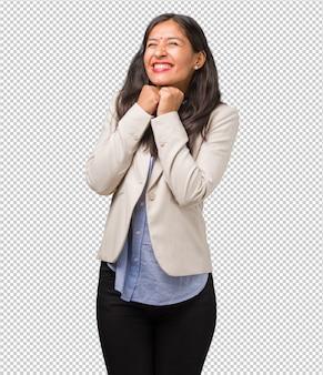 Mulher indiana de negócios jovem muito feliz e animada, levantando os braços, comemorando uma vitória ou sucesso, ganhando na loteria