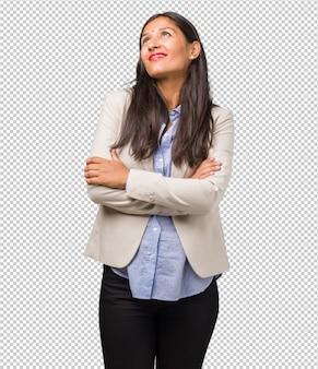 Mulher indiana de negócios jovem, olhando para cima, pensando em algo divertido e tendo uma idéia