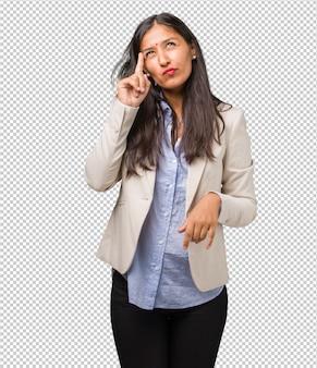 Mulher indiana de negócios jovem, pensando e olhando para cima, confusa com uma idéia, estaria tentando encontrar uma solução