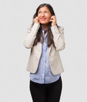 Mulher indiana nova do negócio que cobre as orelhas com as mãos, irritado e cansado de ouvir algum som