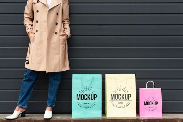 Mulher jovem ao lado de uma maquete de sacola de compras