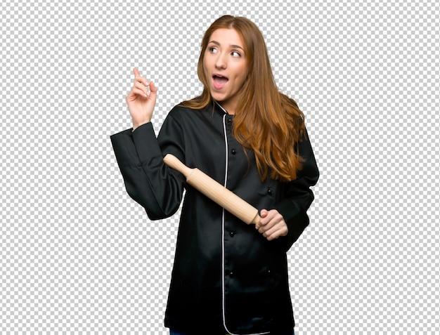 Mulher jovem chef ruiva com a intenção de realizar a solução enquanto levanta um dedo