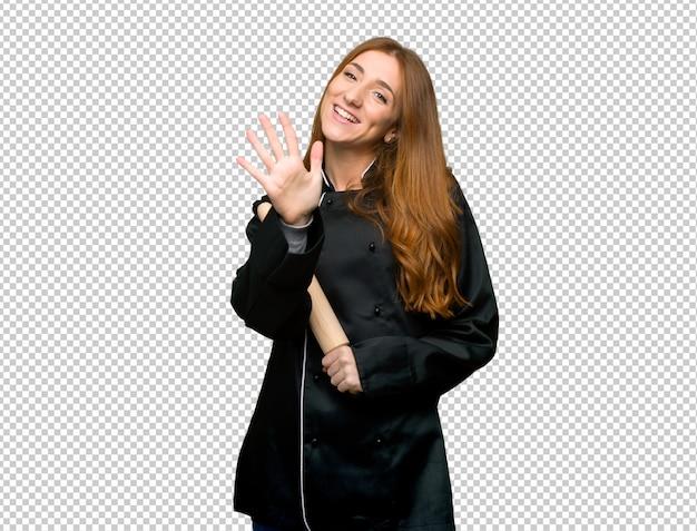 Mulher jovem chef ruiva contando cinco com os dedos