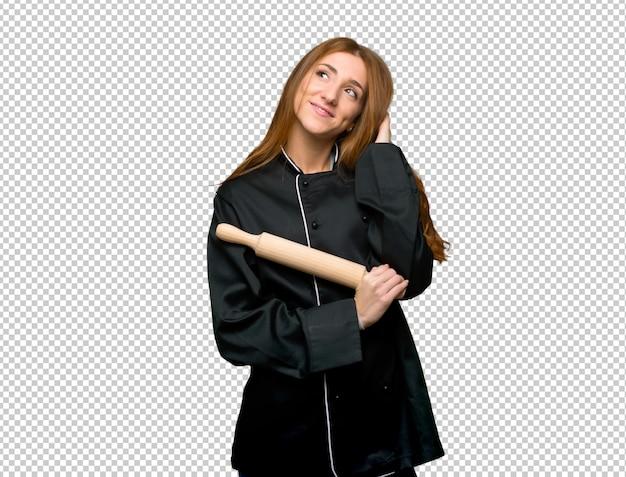 Mulher jovem chef ruiva pensando uma idéia enquanto coçando a cabeça