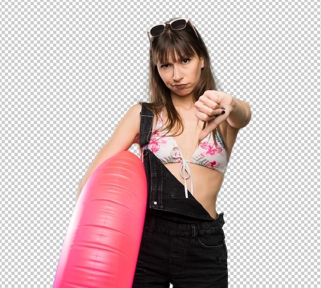 Mulher jovem, em, biquíni, mostrando, polegar baixo, com, expressão negativa