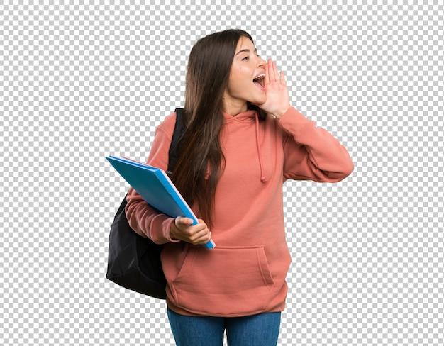 Mulher jovem, estudante, segurando, cadernos, shouting, com, boca largo aberto, para, a, lateral