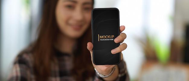 Mulher jovem mostrando maquete de smartphone com fundo desfocado