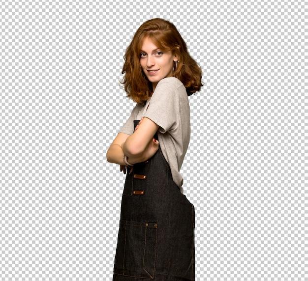 Mulher jovem ruiva com avental com os braços cruzados e olhando para a frente