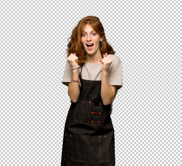 Mulher jovem ruiva com avental comemorando uma vitória na posição de vencedor